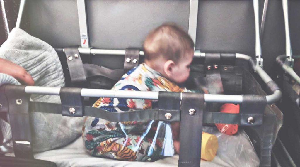 baby-playing-in-airplane-bassinet